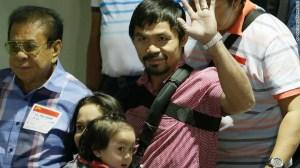 Pacquiao saluda a la multitud al llegar, junto con su esposa Jinkee y su hijo menor Israel (al fondo a la izquierda) el 13 de mayo en el aeropuerto de Filipinas.