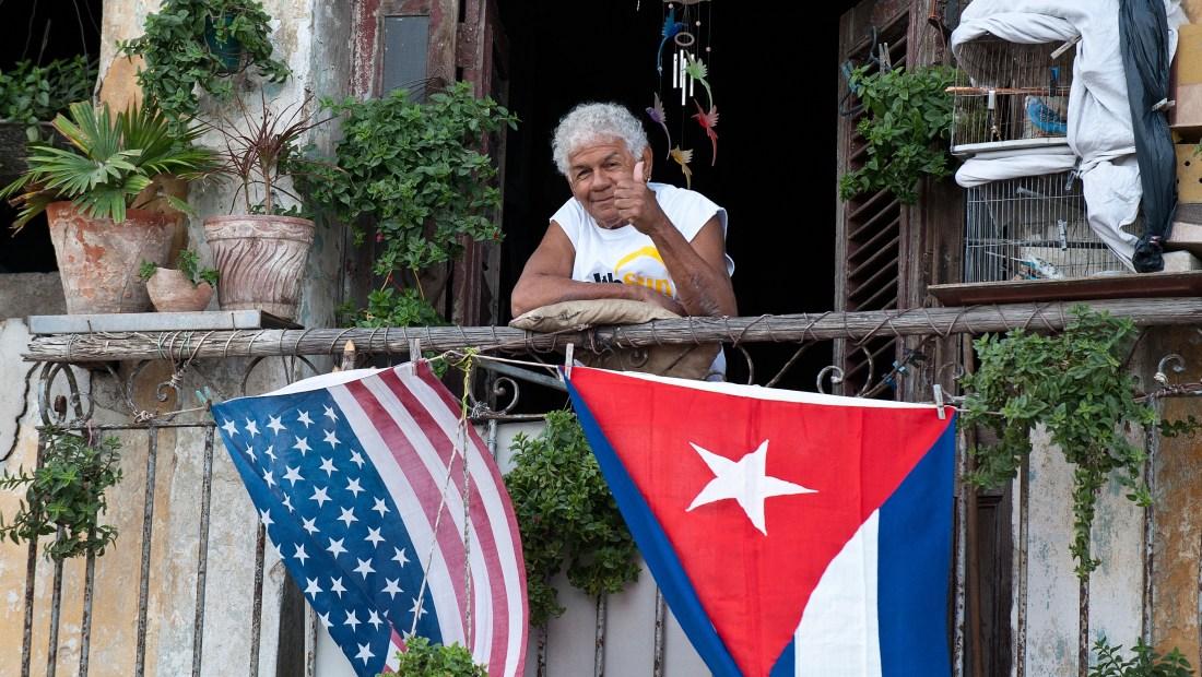 Un cubano saluda desde su balcón decorado con las banderas de Cuba y Estados Unidos en La Habana el 16 de enero de 2015 (Crédito: YAMIL LAGE/AFP/Getty Images)