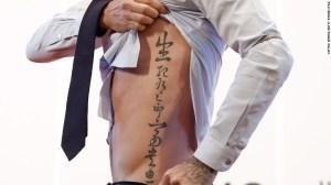 El futbolista británico David Beckham muestra su tatuaje a los aficionados durante su visita a la Universidad de Pekín el 24 de marzo del 2013 en Beijing.