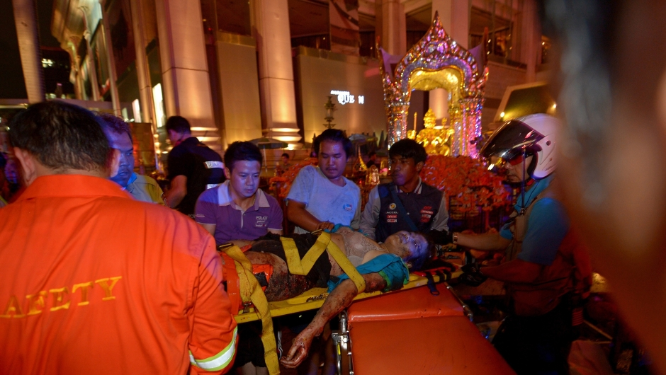 Thai rescue workers transport an injured person (C) after a bomb exploded outside a religious shrine in central Bangkok late on August 17, 2015 killing at least 10 people and wounding scores more. Body parts were scattered across the street after the explosion outside the Erawan Shrine in the downtown Chidlom district of the Thai capital. AFP PHOTO / PORNCHAI KITTIWONGSAKUL (Photo credit should read PORNCHAI KITTIWONGSAKUL/AFP/Getty Images)