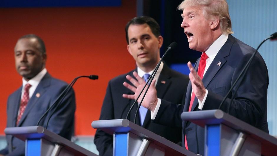 Donald Trump (der.) durante el debate republicano en Cleveland, ante la mirada del gobernador de Wisconsin, Scott Walker (centro) y Ben Carson el 6 de agosto de 2015.