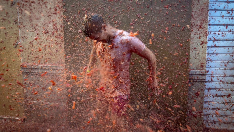 """A reveller is pelted with tomato pulp during the annual """"tomatina"""" festivities in the village of Bunol, near Valencia on August 26, 2015. Some 22,000 revellers hurled 150 tonnes of squashed tomatoes at each other drenching the streets in red in a gigantic Spanish food fight marking the 70th annual """"Tomatina"""" battle. AFP PHOTO / BIEL ALINO (Photo credit should read BIEL ALINO/AFP/Getty Images)"""