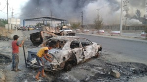 La amenaza terrorista de ISIS: dos niños detrás de un vehículo quemado observan los enfrentamientos entre las fuerzas de seguridad iraquíes y militantes de ISIS en Mosul.