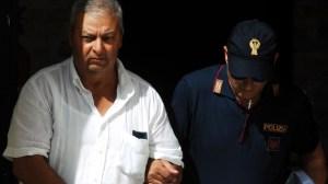 Un policía italiano camina con uno de los sospechosos en Palermo.