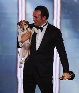 El actor Jean Dujardin alza a Uggie el perro en la tarima de la entrega 84 de los premios de la Academia, el 26 de febrero de 2012. (Crédito: ROBYN BECK/AFP/Getty Images)