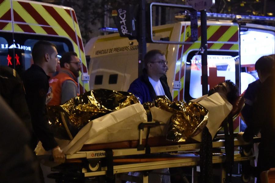 Paramédicos transportan a un espectador herido, quien se encontraba dentro de la sala de conciertos donde fueron tomados como rehenes cientos de personas (AFP/Getty Images).