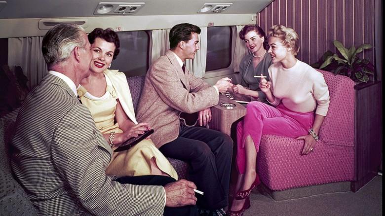 Época anterior a los aviones a reacción – Esta fotografía muestra la vida a bordo de un Douglas DC-7, un avión popular antes de que los aviones a reacción para pasajeros los relevaran. Lo único cómodo a bordo en este avión de motor de émbolo de la década de 1950 era el chico con una chaqueta de tweed y la luz para las damas.