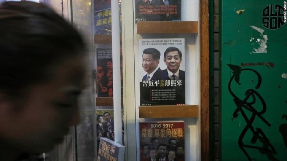 Una mujer pasa junto a un libro en el que aparece en la portada el presidente de China, Xi Jinping, a la izquierda, el exmiembro del Buró Político y el líder del partido de la ciudad de Chongqing, Bo Xilai, en la entrada de la librería cerrada Causeway Bay, el domingo, 3 de enero de 2016.