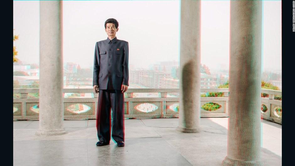 """Guía del Parque Tonghungsan, Hamhung – """"En cualquier lugar al que íbamos primero había un guía que presentaba, por ejemplo, la historia de la fábrica, luego nos mostraba el museo de la fábrica y luego podíamos ir y conocer a las personas de verdad. Simplemente me encanta esta foto porque él era tan alto y porque su ropa es tan gráfica y encaja perfectamente con las columnas que lo rodean. Por lo demás, traté de evitar fotografiar a los guías de la manera en que todos los que van a Corea del Norte los ve""""."""