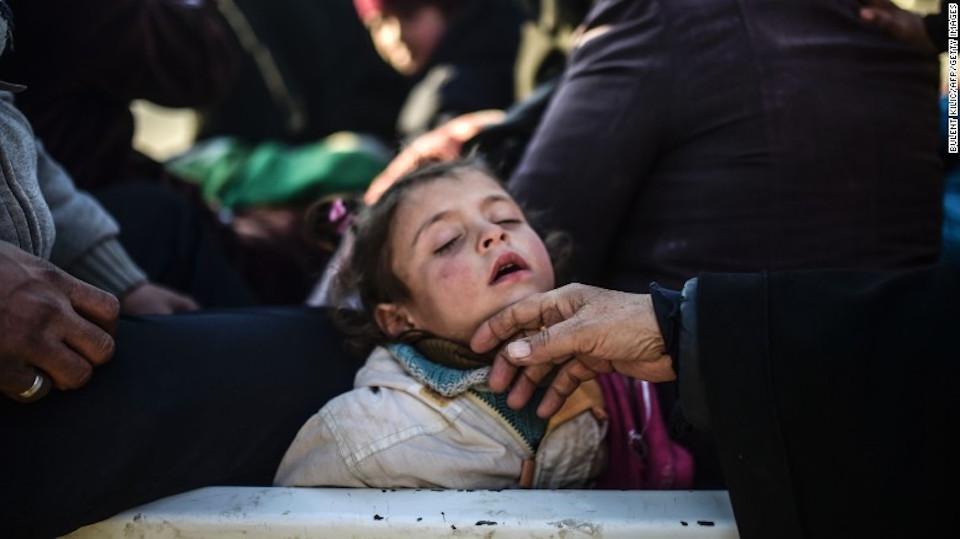 Una niña siria duerme mientras su familia huye de la sitiada ciudad de Alepo hacia la frontera con Turquía, el 6 de febrero de 2016.