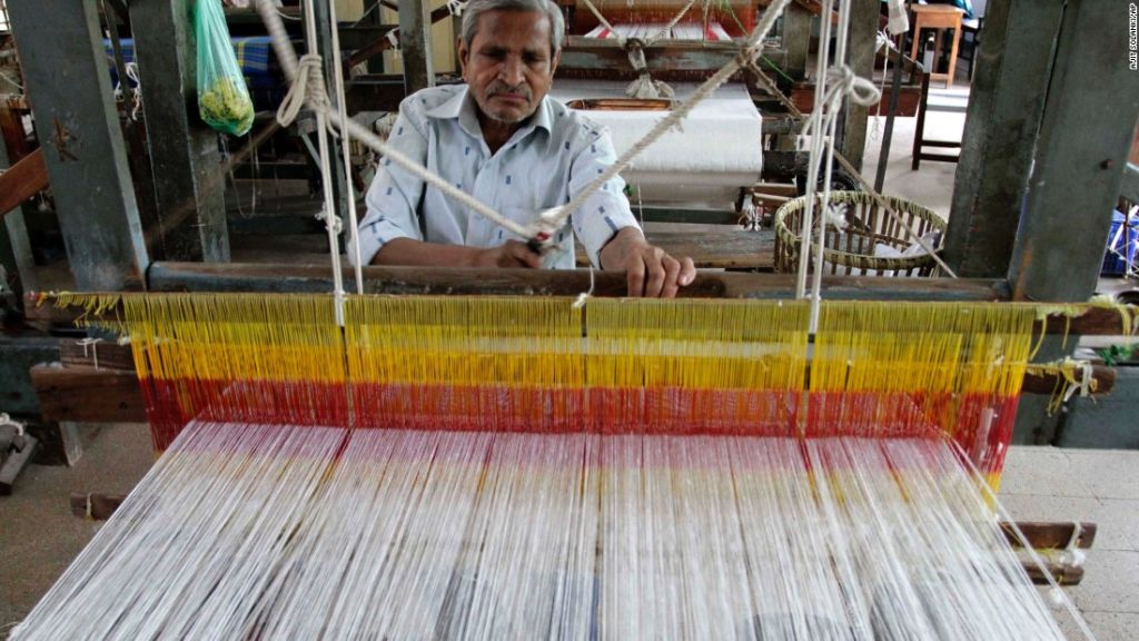 Un hombre indio teje en una fábrica de telares manuales en Ahmadabad, India.