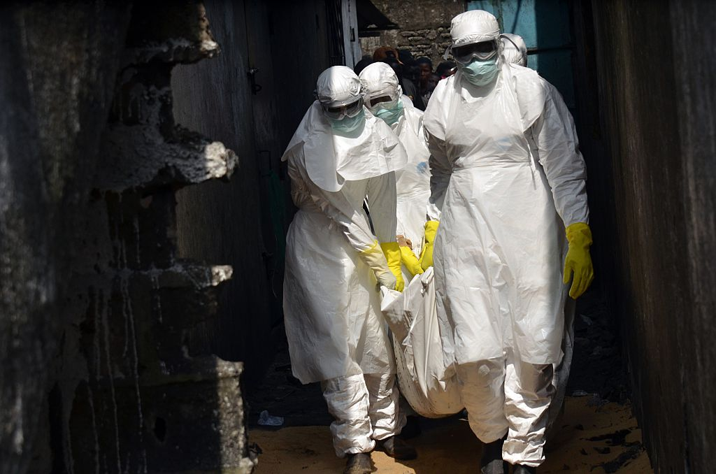 Red cross workers, wearing protective suits, carry the body of a person who died from Ebola during a burial with relatives of the victims of the virus, in Monrovia, on January 5, 2015. Schools in Ebola-ravaged Liberia will reopen in February, six months after they were closed in a bid to contain the spread of the killer virus, the education ministry said on January 5, 2015. The worst Ebola outbreak on record has killed 8,153 people over the past year. Liberia has seen the highest fatality rate with 3,471 deaths, followed by Sierra Leone and Guinea. AFP PHOTO / ZOOM DOSSO (Photo credit should read ZOOM DOSSO/AFP/Getty Images)