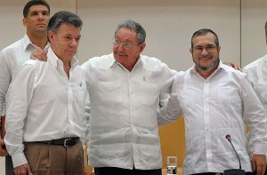 "PAZ RECONCILIACIÓN COLOMBIA Cuban President Raul Castro (C) embraces Colombian President Juan Manuel Santos (L) and the head of the FARC guerrilla Timoleon Jimenez, aka Timochenko (R), during a meeting in Havana on September 23, 2015. The Colombian government and FARC rebels announced a key breakthrough in their nearly three-year peace talks Wednesday with the signing of a deal on justice for crimes committed during the five-decade conflict. The deal includes the creation of special courts and a broad amnesty, though this will not cover ""crimes against humanity, serious war crimes"" and other offenses including kidnappings, extrajudicial executions and sexual abuse, said officials from Cuba and Norway, the guarantors in the talks. AFP PHOTO / Yamil Lage (Photo credit should read YAMIL LAGE/AFP/Getty Images)"