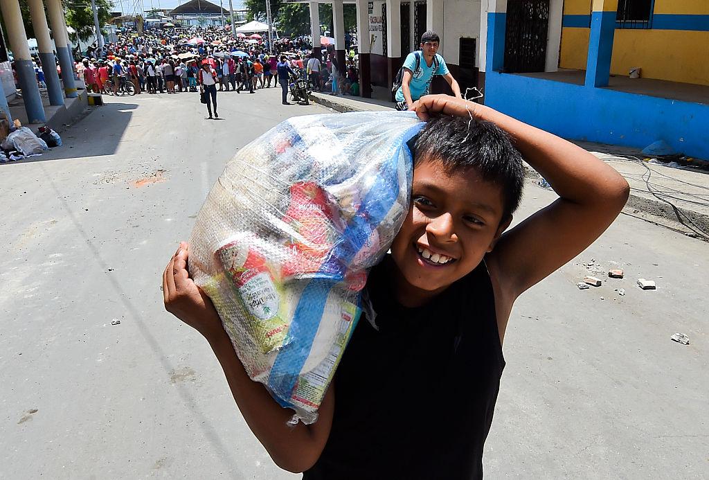 Un niño ecuatoriano sonríe después de recibir provisiones de comida en Manta, Ecuador. El espíritu del pueblo ecuatoriano está más fuerte que nunca tras el devastador terremoto del 16 de abril. (Crédito: LUIS ACOSTA/AFP/Getty Images)
