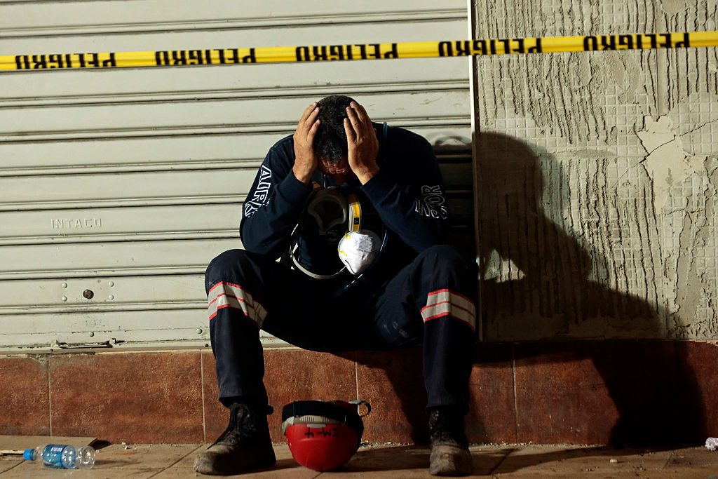A rescuer takes a break after helping in the search for earthquake victims in Manta on April 20, 2016. The death toll from Ecuador's earthquake was set to rise sharply after authorities warned that 1,700 people were still missing and anger gripped families of victims trapped in the rubble. A 6.1-magnitude earthquake struck off the coast of Ecuador Wednesday, sowing new panic four days after a more powerful quake killed more than 525 people, with hundreds still missing. / AFP / Juan Cevallos (Photo credit should read JUAN CEVALLOS/AFP/Getty Images)