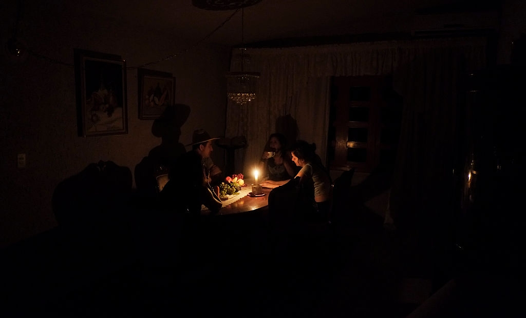 A family sit at a candle lit table in the state of Barinas, 600 km west of Caracas on April 25, 2016. Recession-hit Venezuela will turn off the electricity supply in its 10 most populous states for four hours a day for 40 days to deal with a severe power shortage, the government said. It is the latest drastic measure by the government in a crisis that already has Venezuelans queuing for hours to buy scarce supplies in shops. / AFP / JUAN BARRETO (Photo credit should read JUAN BARRETO/AFP/Getty Images)