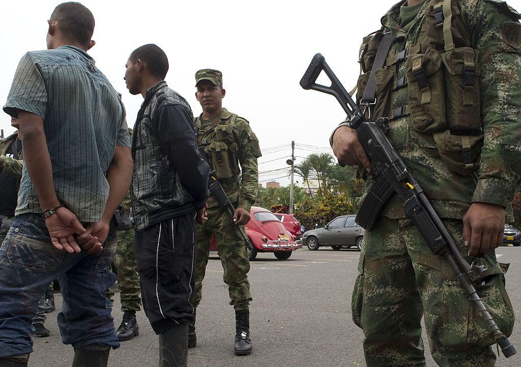 Demobilized fighters of the 36th Column of the FARC leftist guerrillas are escorted by Colombian soldiers during a press conference on September 20, 2012 in Medellin, Antioquia department, Colombia. Seven FARC members were demobilized after surrendering their weapons. AFP PHOTO/Raul ARBOLEDA (Photo credit should read RAUL ARBOLEDA/AFP/GettyImages)
