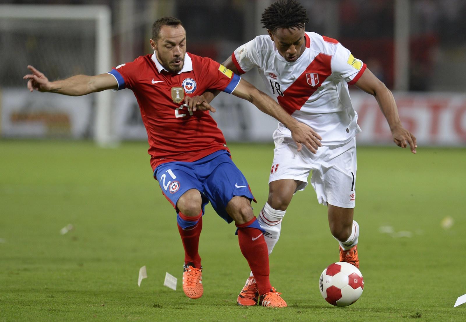 Marcelo Díaz (izquierda) y André Carrillo, de Perú, disputan el balón durante su partido de clasificación para el Mundial 2018 en el estadio Estadio Nacional de Lima, el 13 de octubre de 2015. Crédito: ERNESTO BENAVIDES / AFP / Getty Images.