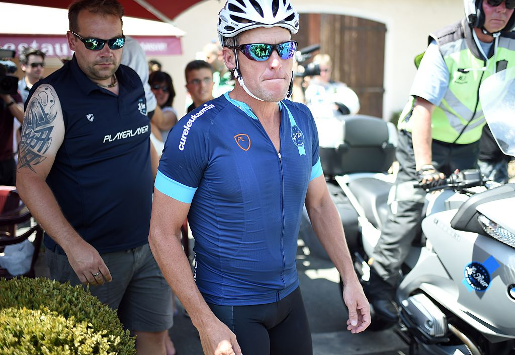 """US cyclist Lance Armstrong walks to his bicycle in Villefranche-d'Albigeois, southwest France, where he stopped for lunch during as he rides a stage of The Tour De France for a leukaemia charity, a day ahead of the competing riders, on July 16, 2015. For the first time since he was stripped of his seven Tour de France titles, disgraced cyclist Lance Armstrong rode a stage of the famous race for charity. Armstrong, 43, was riding a 198-kilometre (123-mile) stage a day ahead of the competing riders for a leukaemia charity but cycling officials have branded the exercise """"disrespectful"""". AFP PHOTO / STEPHANE DE SAKUTIN (Photo credit should read STEPHANE DE SAKUTIN/AFP/Getty Images)"""