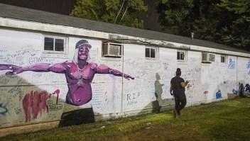 Una persona que lee los mensajes escritos en la pared junto a la tienda donde Alton Sterling murió a tiros el 6 de julio de 2016, en Baton Rouge, Louisiana. Crédito: Mark Wallheiser / Getty Images.