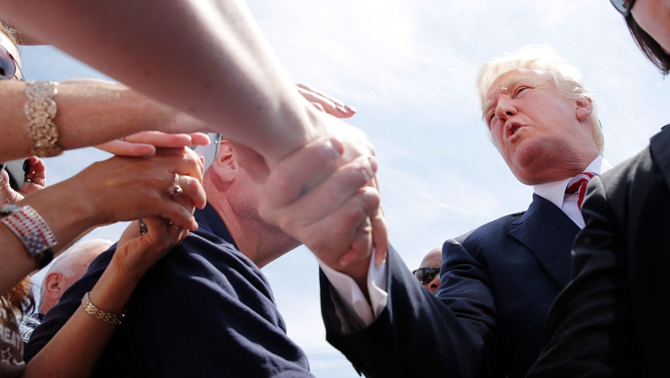 Republican presidential nominee Donald Trump greets supporters after arriving in Cleveland on the third day of the Republican National Convention on July 20, 2016, in Cleveland, Ohio. / AFP / DOMINICK REUTER (Photo credit should read DOMINICK REUTER/AFP/Getty Images)