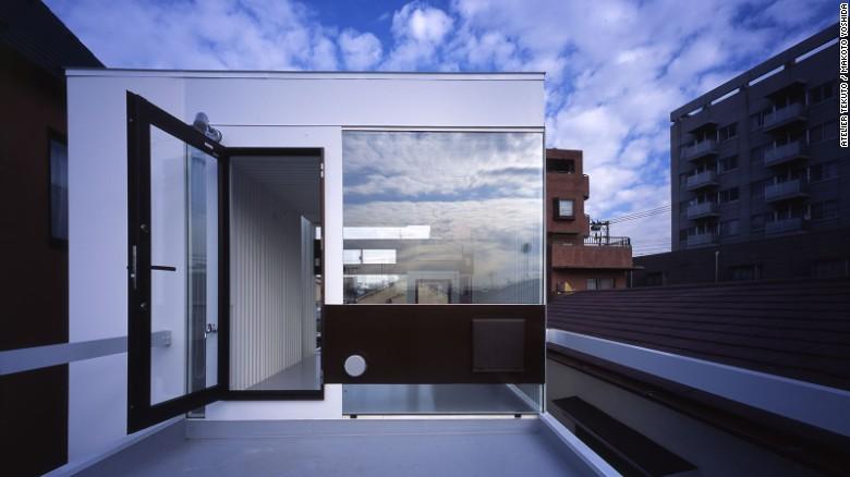 Una casa de estilo industrial diseñada por Atelier Tekuto, 'Wafers' hace uso del hormigón reforzado, acero y ventanas altamente reflectoras.