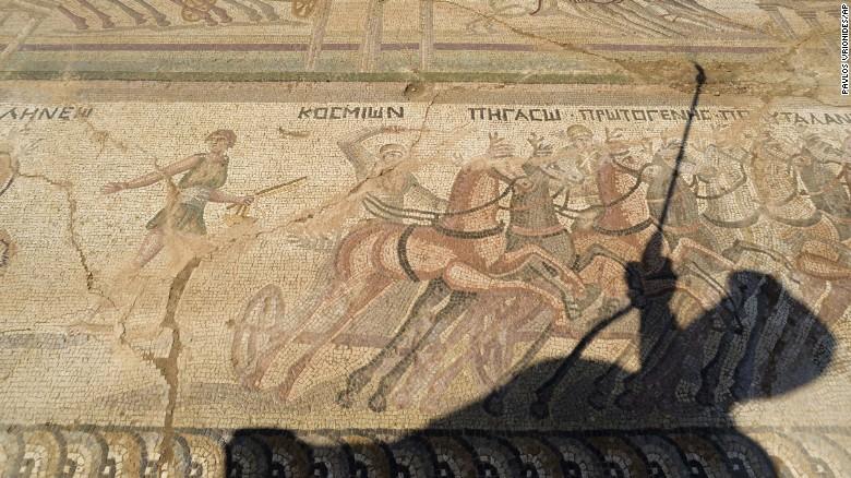 La sombra de Fryni Hadjichristofi cae sobre el mosaico en el piso, que representa escenas de la Antigua Roma.