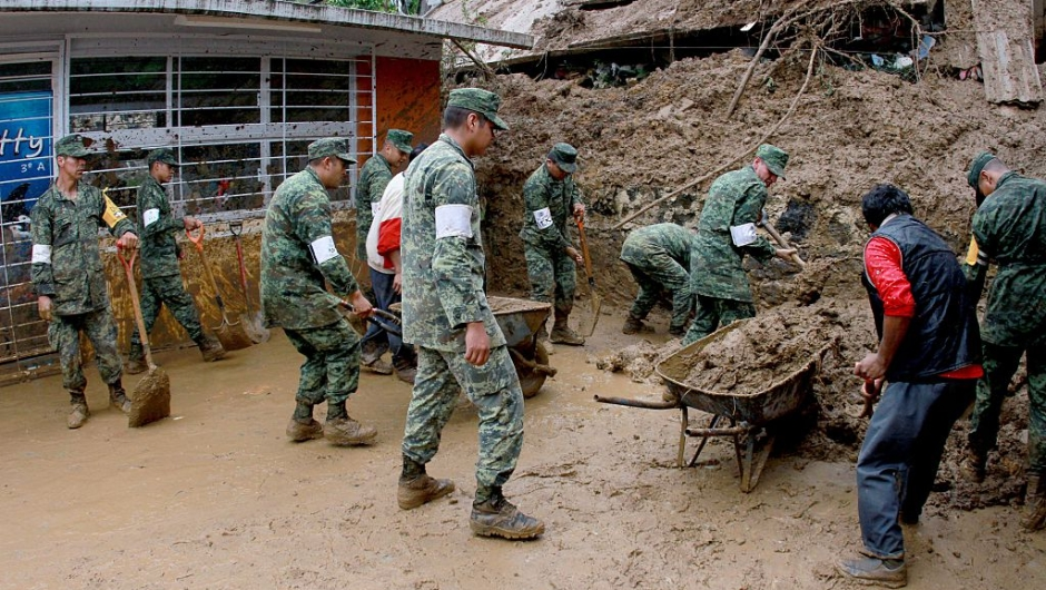 Mexican soldiers help dig out damaged homes in Xalapa community, Veracruz, Mexico on August 6, 2016. Six people died in the eastern Mexican state of Veracruz after their homes were buried by landslides following heavy rains from Earl, which reached Mexican territory on Thursday as a tropical storm and Saturday was only a remnant low pressure. / AFP / EDUARDO MURILLO (Photo credit should read EDUARDO MURILLO/AFP/Getty Images)