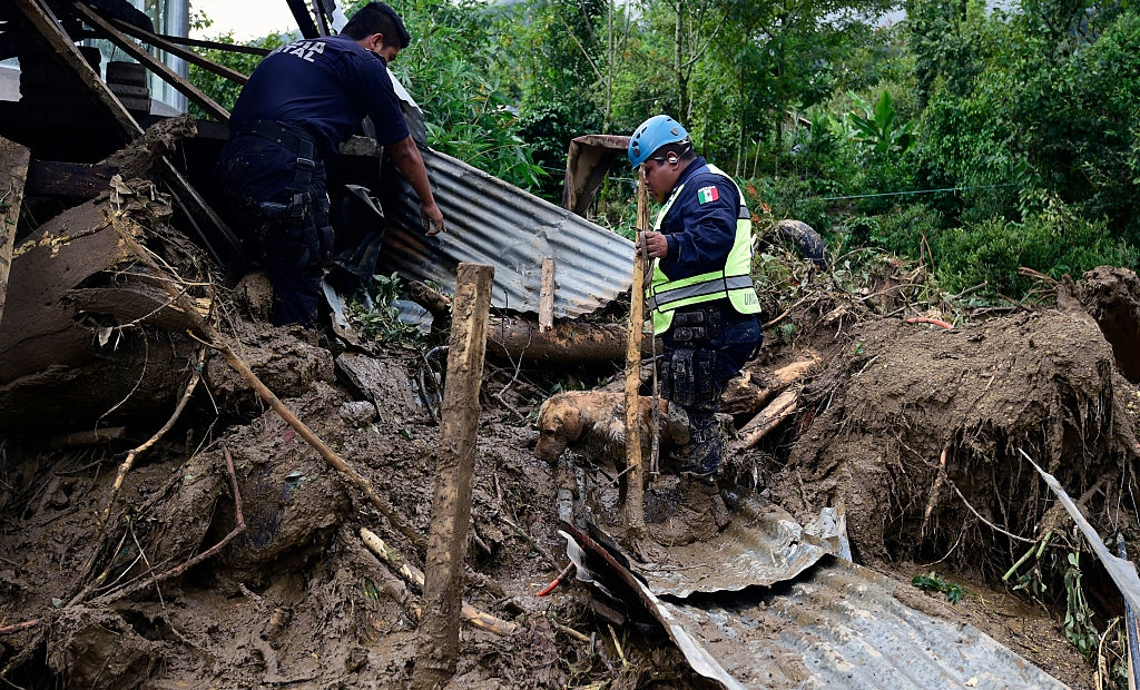 A Federal Police rescuer and his sniffer dog search for buried corpses amid the damage caused by a landslide ensuing the passage of Tropical Storm Earl in the community of Xaltepec, Puebla state, eastern Mexico on August 8, 2016. A total of 29 people died in the communities of Xaltepec, Tlaola and Huauchinango in the Mexican state of Puebla after their homes were buried by landslides following heavy rains from Earl, which reached Mexican territory on Thursday as a tropical storm and Saturday was only a remnant low pressure. / AFP / AE / ALFREDO ESTRELLA (Photo credit should read ALFREDO ESTRELLA/AFP/Getty Images)