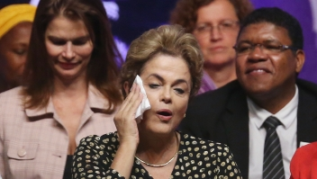 BRASILIA, BRAZIL - MAY 10: Embattled Brazilian President Dilma Rousseff (C) wipes her face with a handkerchief after speaking at a women's rights conference on May 10, 2016 in Brasilia, Brazil. Rousseff is facing an impeachment vote in the Senate tomorrow that could force her to step down from the presidency for 180 days and face trial. (Photo by Mario Tama/Getty Images)