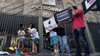 Activists hold signs during a protest against corruption outside state-owned oil giant Petrobras in Rio de Janeiro on December 16, 2014. AFP PHOTO/VANDERLEI ALMEIDA (Photo credit should read VANDERLEI ALMEIDA/AFP/Getty Images)