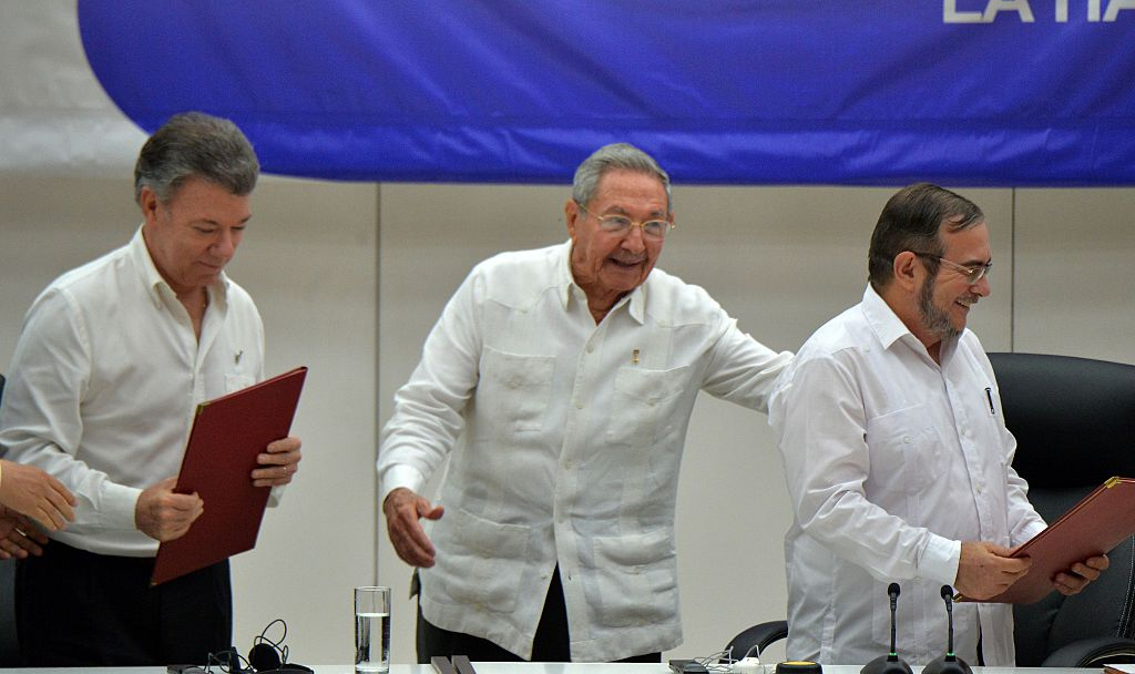"""Colombia's President Juan Manuel Santos (L), Cuban President Raul Castro (C) and Timoleon Jimenez, aka """"Timochenko"""" (R), head of the FARC leftist guerrilla, during the signing of the ceasefire in Havana on June 23, 2016. Colombia's government and the FARC guerrilla force signed a definitive ceasefire Thursday, taking one of the last crucial steps toward ending Latin America's longest civil war. / AFP / ADALBERTO ROQUE (Photo credit should read ADALBERTO ROQUE/AFP/Getty Images)"""
