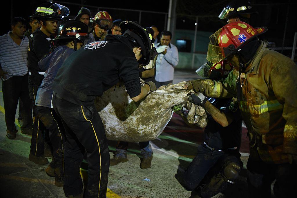 Los bomberos cargan un cuerpo recuperado de los escombros en Villa Nueva, Guatemala. (JOHAN ORDONEZ/AFP/Getty Images)