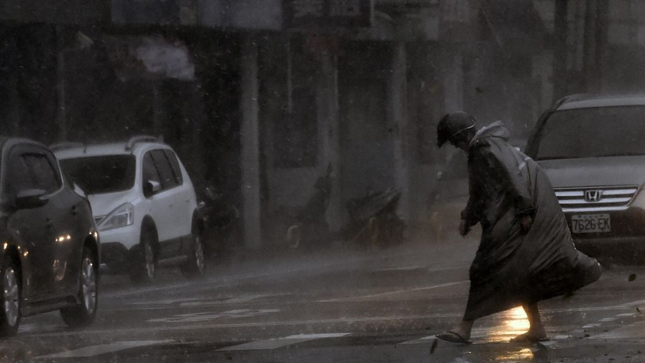 TOPSHOT - A man walks during a storm in Xindian district, New Taipei City, as Typhoon Megi hit eastern Taiwan on September 27, 2016. Taiwan went into shutdown on September 27 as the island faces its third typhoon in two weeks, with thousands evacuated, schools and offices closed across the island and hundreds of flights disrupted. / AFP / SAM YEH (Photo credit should read SAM YEH/AFP/Getty Images)