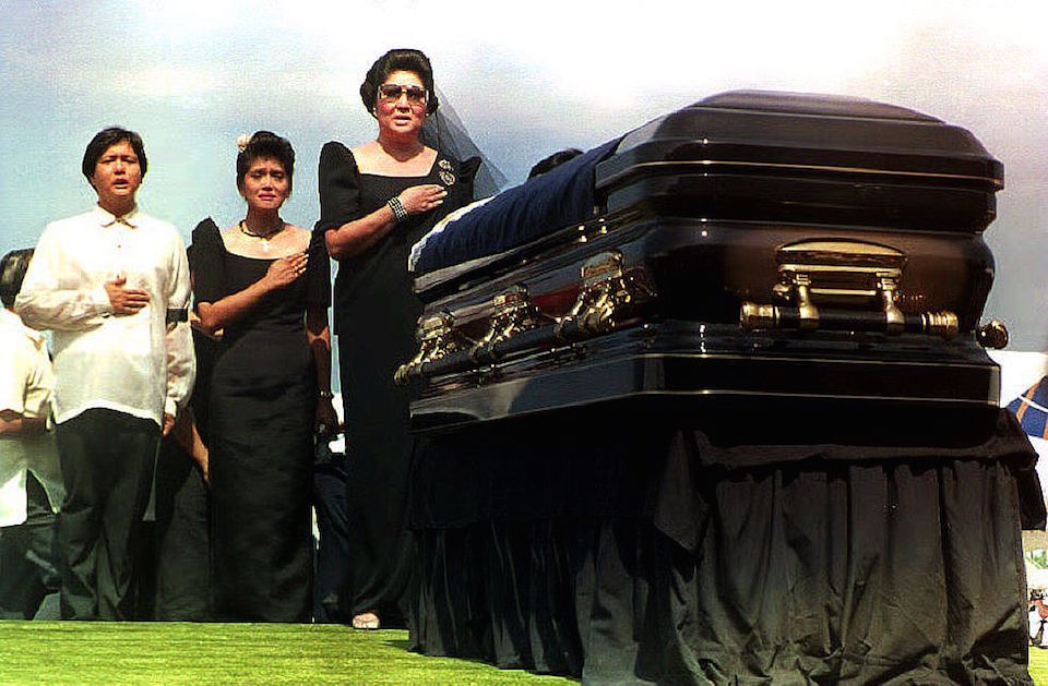 LAOAG, PHILIPPINES: Former Philippine First Lady Imelda Marcos (R) and her son Ferdinand Marcos Jr. (L) and daughter Imee Manotoc (C) sing the Philippine national anthem before the flag-draped coffin bearing the remains of former Philippine President Ferdinand Marcos during arrival ceremonies at Laoag's airport 07 September 1993. (Photo credit should read ROMEO GACAD/AFP/Getty Images)