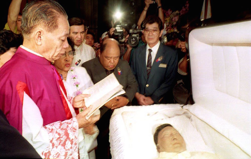 El regreso a Filipinas,. HONOLULU, HI - SEPTEMBER 4: Msgr. Domingo Nebres (L) flanked by the sister of the late Philippine President Ferdinand Marcos, Fortuna Barba, recites prayers over the open casket of Marcos. Services began early 04 September 1993 preparing to take Marcos' body back to be buried in the Philippines. He died in exile in Honolulu in 1989. (Photo credit should read GEORGE F.LEE/AFP/Getty Images)