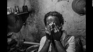 Paula, de 48 años, rompe a llorar cuando recuerda cómo ha cambiado la vida en Venezuela en los últimos años. Mientras tomaba esta foto ella cocinaba patas de gallina para el almuerzo, una comida que solía darle al perro.