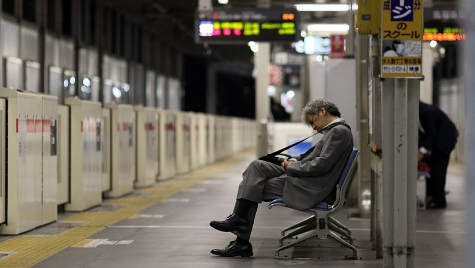 """TO GO WITH """"JAPAN-LABOUR-LIFESTYLE-ECONOMY"""" BY NATSUKO FUKUE This picture taken on May 22, 2015 shows a businessman sleeping on a bench at a Tokyo train station. Japan's push to take away overtime from high-paid workers has critics warning it will aggravate a problem synonymous with the country's notoriously long working hours -- karoshi, or death from overwork. AFP PHOTO / Yoshikazu TSUNO (Photo credit should read YOSHIKAZU TSUNO/AFP/Getty Images)"""