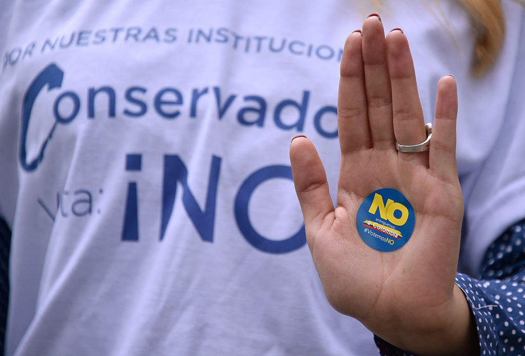"A woman supporting the vote for ""No"" in the upcoming referendum, takes part in a motorcade in Bogota, on October 1, 2016. Colombians will vote a referendum Sunday on whether to ratify a historic peace accord to end the 52-year war between the state and the communist FARC rebels. The accord will effectively end what is seen as the last major armed conflict in the Western Hemisphere. The war has killed hundreds of thousands of people and displaced millions. / AFP / GUILLERMO LEGARIA (Photo credit should read GUILLERMO LEGARIA/AFP/Getty Images)"