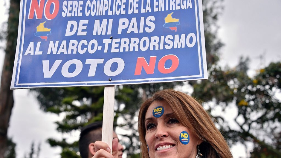 """A woman holds a sign reading """"I won't be accomplice of the handing of my country to drug-terrorism. I vote No"""" during a motorcade ahead of Sunday referendum in Bogota, on October 1, 2016. Colombians will vote a referendum Sunday on whether to ratify a historic peace accord to end the 52-year war between the state and the communist FARC rebels. The accord will effectively end what is seen as the last major armed conflict in the Western Hemisphere. The war has killed hundreds of thousands of people and displaced millions. / AFP / GUILLERMO LEGARIA (Photo credit should read GUILLERMO LEGARIA/AFP/Getty Images)"""
