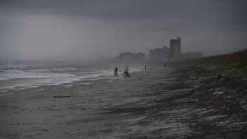People bike on the beach ahead of hurricane Matthew in Atlantic Beach, Florida, on October 5, 2016. The United States began evacuating coastal areas as Hurricane Matthew churned toward the Bahamas, after killing at least nine people in the Caribbean in a maelstrom of wind, mud and water. / AFP / Jewel SAMAD (Photo credit should read JEWEL SAMAD/AFP/Getty Images)