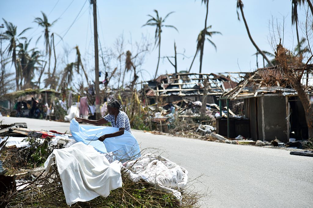 """A woman displays her clothes in front of her destroyed house in Les Cayes, Haiti on October 10, 2016, following the passage of Hurricane Matthew. Haiti faces a humanitarian crisis that requires a """"massive response"""" from the international community, the United Nations chief said , with at least 1.4 million people needing emergency aid following last week's battering by Hurricane Matthew. / AFP / HECTOR RETAMAL (Photo credit should read HECTOR RETAMAL/AFP/Getty Images)"""