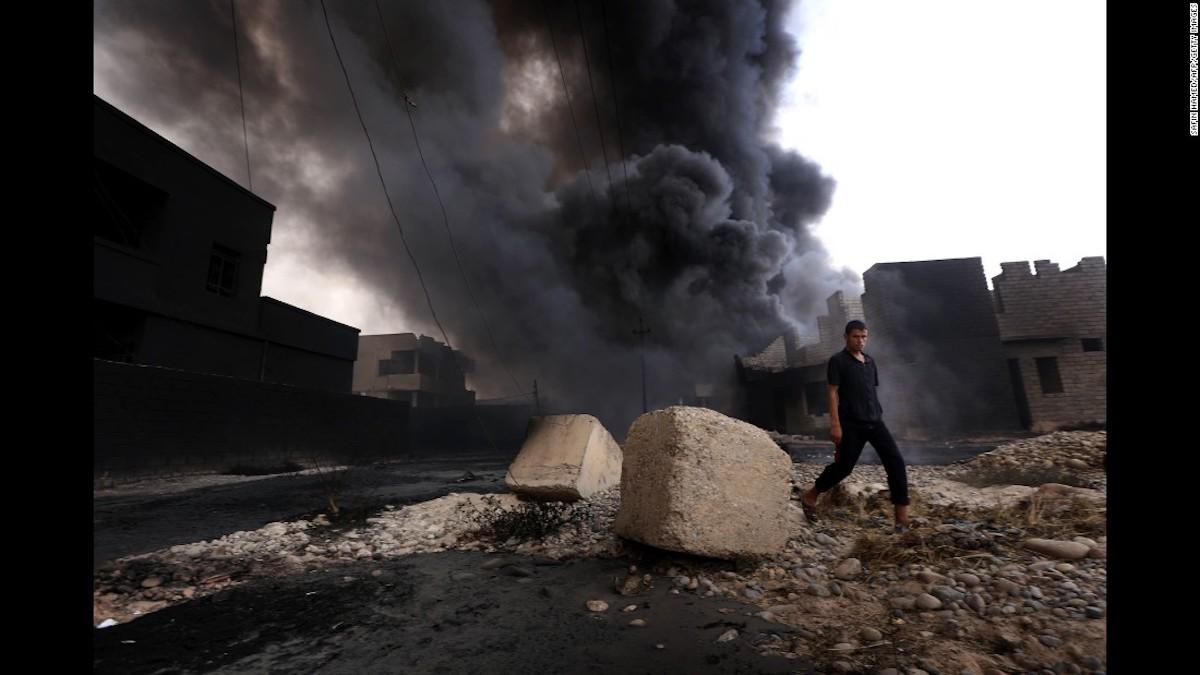 Un hombre Iraquí camina cerca de una columna de humo que sale de los pozos de petróleo incendiados por ISIS antes de huir de la región productora de crudo de Qayyarah en agosto 30 de 2016.