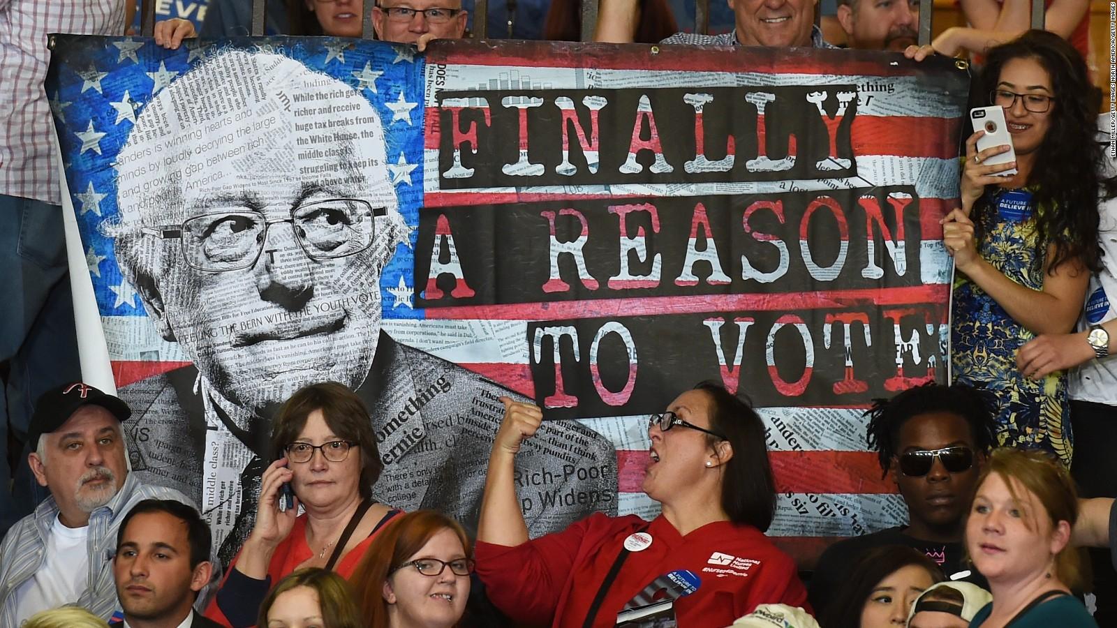 Seguidores de Bernie Sanders sostienen un afiche durante un evento de campaña del excandidato demócrata.