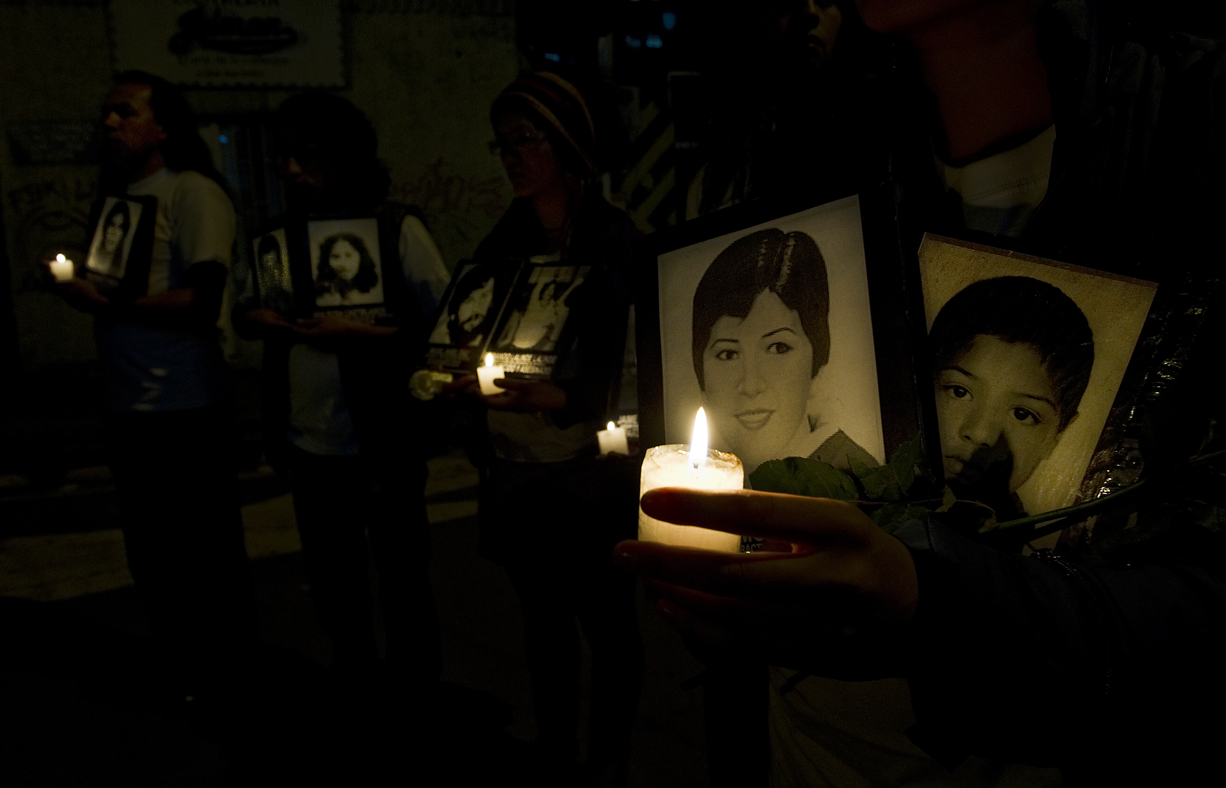 """Relatives of missing persons in Colombia hold photographs and candles during a protest in Bogota on May 26, 2011. The drama of enforced disappearance in Colombia has reached numbers that the representative in Colombia of the United Nations High Commissioner for Human Rights, Christian Salazar, described as """"chilling"""". At least 26,500 cases have been reported to the prosecutor. AFP PHOTO/Luis Acosta (Photo credit should read LUIS ACOSTA/AFP/Getty Images)"""