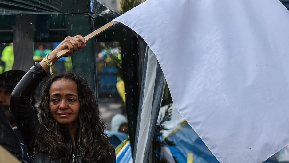 TOPSHOT - A woman cries as she flutters a white flag during a demo for the immediate implementation of the agreement between the Colombian government and the FARC guerrillas at Bolivar Square in Bogota on November 18, 2016. / AFP / Luis Acosta (Photo credit should read LUIS ACOSTA/AFP/Getty Images)