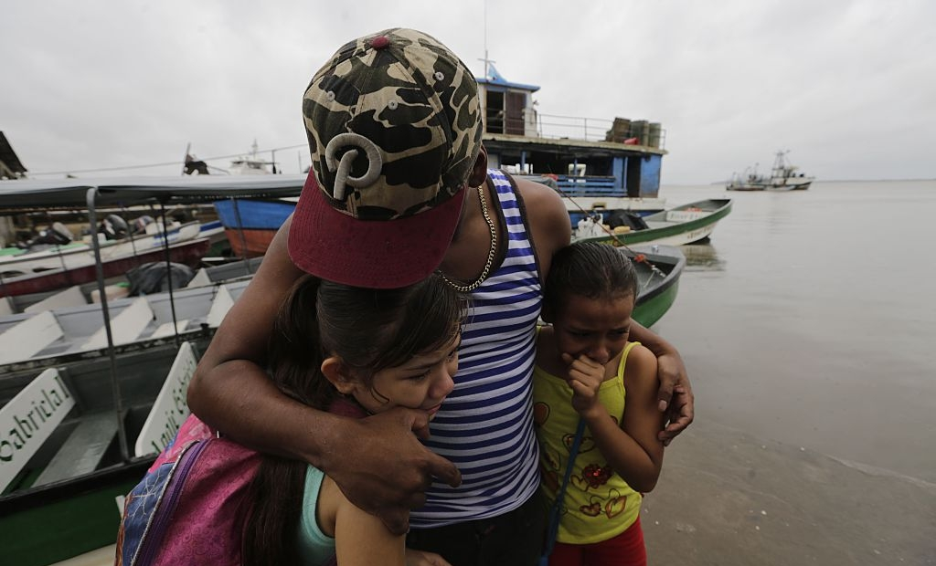 """TOPSHOT - Two children seek cover under the embrace of their father before Hurricane Otto arrives in Bluefields, Nicaragua on November 23, 2016. A Caribbean storm verging on a hurricane spun towards the coasts of Costa Rica and Nicaragua on Wednesday, prompting evacuations and red alerts ahead of """"life-threatening"""" flash flooding. / AFP / INTI OCON (Photo credit should read INTI OCON/AFP/Getty Images)"""