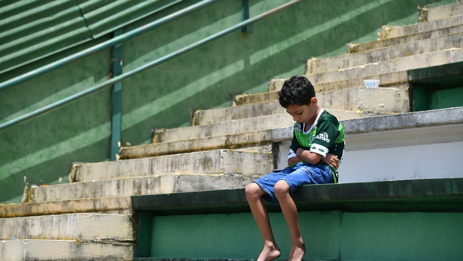 A boy sits alone on the stands during a tribute to the players of Brazilian team Chapecoense Real who were killed in a plane accident in the Colombian mountains, at the club's Arena Conda stadium in Chapeco, in the southern Brazilian state of Santa Catarina, on November 29, 2016. Players of the Chapecoense were among 81 people on board the doomed flight that crashed into mountains in northwestern Colombia, in which officials said just six people were thought to have survived, including three of the players. Chapecoense had risen from obscurity to make it to the Copa Sudamericana finals scheduled for Wednesday against Atletico Nacional of Colombia. / AFP / Nelson ALMEIDA (Photo credit should read NELSON ALMEIDA/AFP/Getty Images)