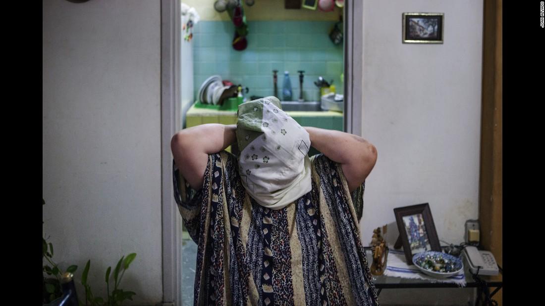 Una mujer de 72 años llamada Shahira lucha para ponerse un velo islámico. Ella era una cristiana activa hasta hace tres años. Ahora es miembro del Comité Islámico Cubano de mujeres.