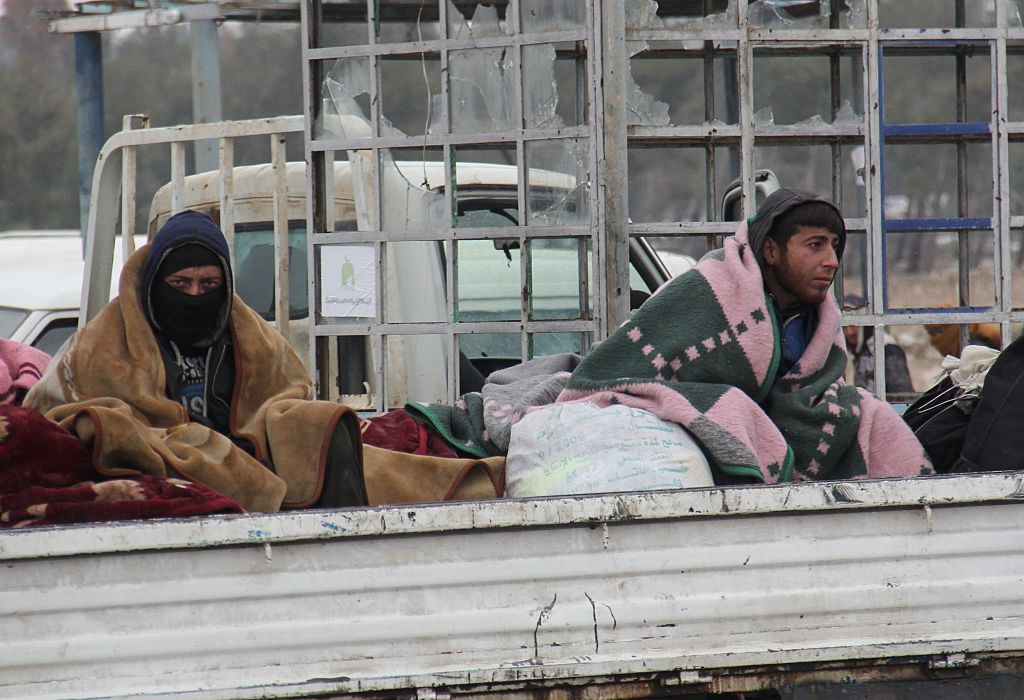 Syrians being evacuated from Aleppo are seen in the back of a pick up truck as it drives through a rebel-held territory near Rashidin, west of the embattled city, on December 22, 2016. Convoys carried opposition fighters out of the last rebel pocket of Aleppo in the final phase of an evacuation clearing the way for Syria's army to retake the city. As part of the Aleppo evacuation deal, it was agreed that some residents would be allowed to leave Fuaa and Kafraya, two Shiite-majority villages in northwestern Syria that are under siege by the Sunni Muslim rebels. / AFP / Omar haj kadour (Photo credit should read OMAR HAJ KADOUR/AFP/Getty Images)